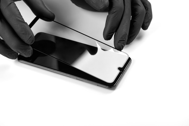 Een man installeert een beschermend glas op het scherm van een smartphone.