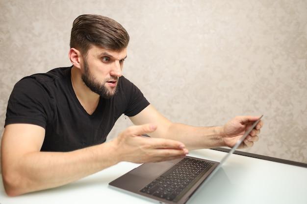 Een man is bezig met belangrijk werk op een laptop