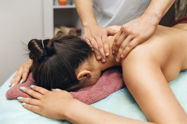 Een man is een chiropractor die een massage geeft aan een vrouw in de nek en trapeziusspieren in zijn kantoor