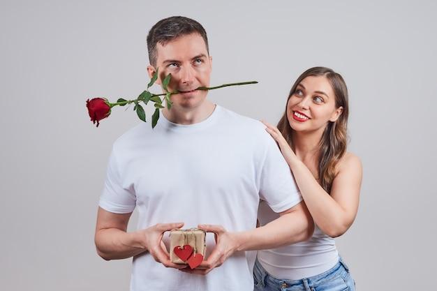 Een man is sceptisch over een feestdag, een cadeau, terwijl een verliefde vrouw naar hem kijkt en hem bij zijn schouders omhelst.