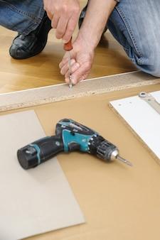 Een man is thuis de meubels aan het monteren.