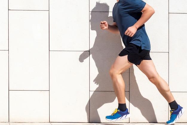 Een man joggen op een track met zijn schaduw op de muur.
