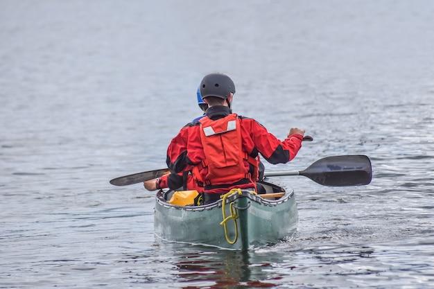Een man kajakt met een vriend op windermere lake, windermere, lake district in cumbria