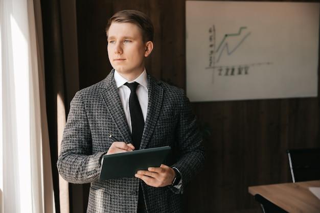 Een man-kantoormedewerker staat op kantoor en schrijft informatiewerk op met documenten die op kantoor werken