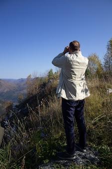 Een man kijkt door veldglazen staande op een bergtop.