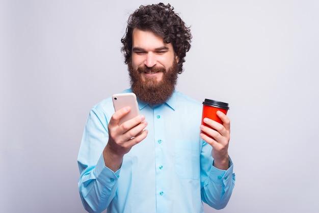 Een man kijkt en lacht naar zijn telefoon en houdt een beker met warme drank vast
