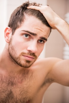 Een man kijkt in de spiegel en doet een kapsel op zijn hoofd.