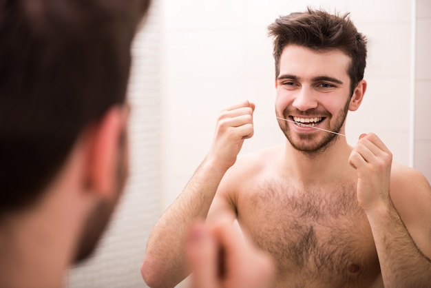 Een man kijkt in de spiegel en flosst zijn tanden.