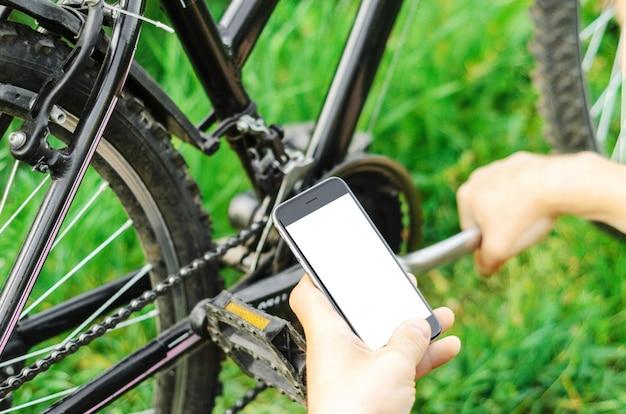 Een man kijkt in de telefoon en repareert een mountainbike op een bosweg