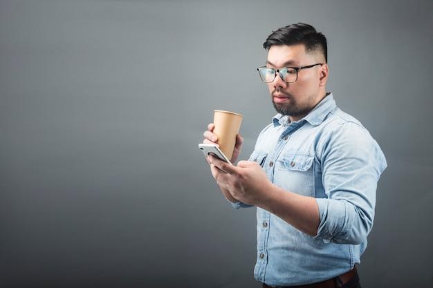 Een man kijkt naar de telefoon met verbazing op een grijze achtergrond