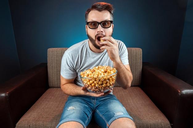 Een man kijkt naar een film of serie met een 3d-bril, een blauwe muur. het concept van een bioscoop, films, emoties, verrassing, vrije tijd, streaming platforms.