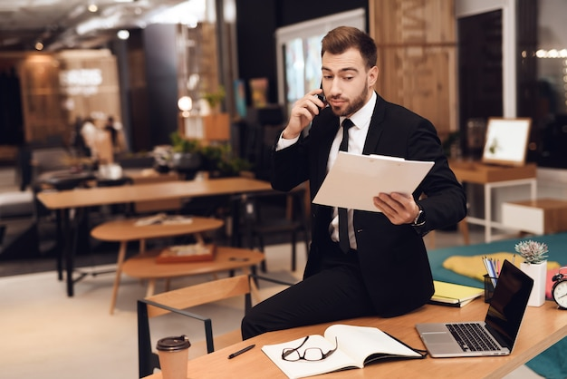 Een man kijkt naar papierwerk en praat aan de telefoon.