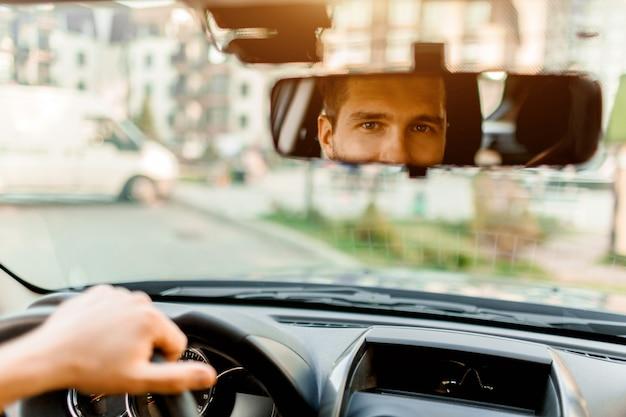 Een man kijkt uit het achterruit. in zijn auto. vervoer concept
