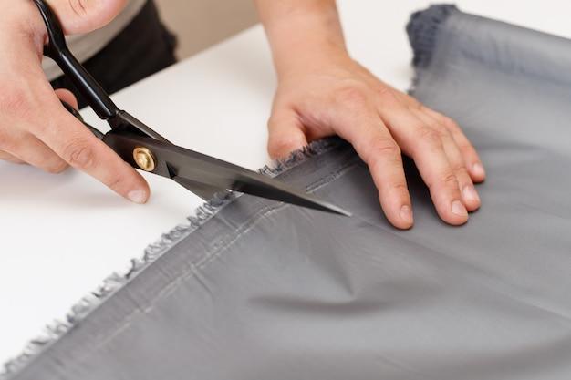Een man knipt stof op tafel met een schaar. detailopname