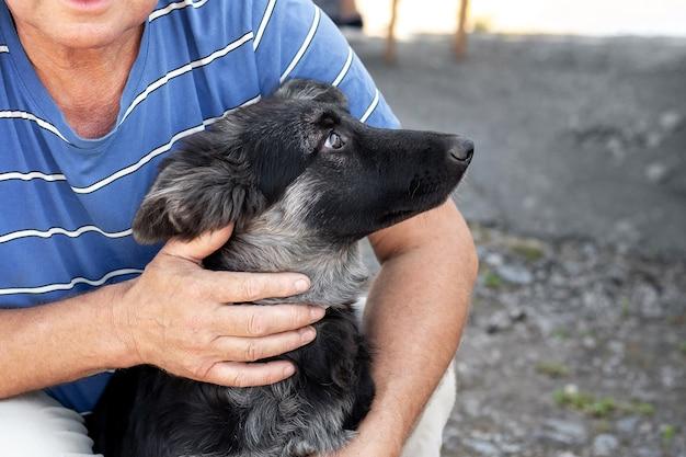 Een man knuffelt een hondenras oost-europese herder. de man houdt van de hond
