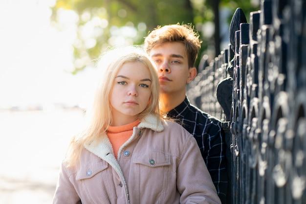 Een man knuffelt zacht een vrouw, een jongen en een meisje staan dicht bij het hek van park en kijken ernaar uit.