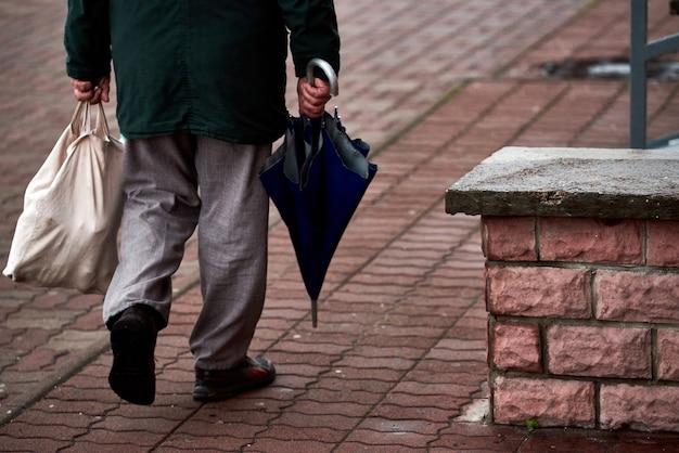 Een man komt uit een winkel met een stoffen torba en een paraplu. straat foto. slecht weer