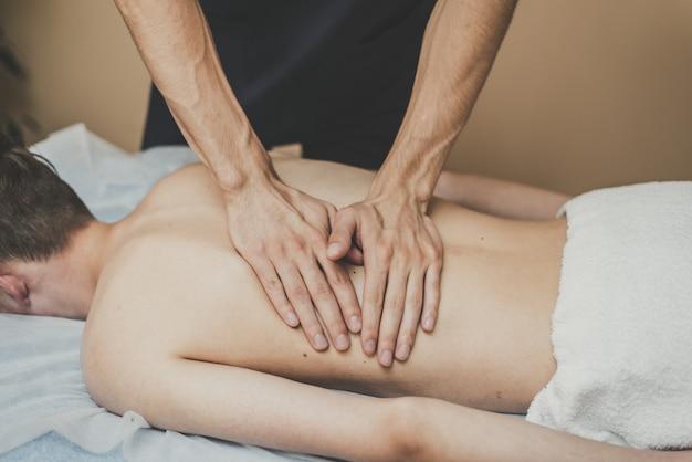 Een man krijgt een rugmassage. ontspanning op de massagetafel. mooi getint