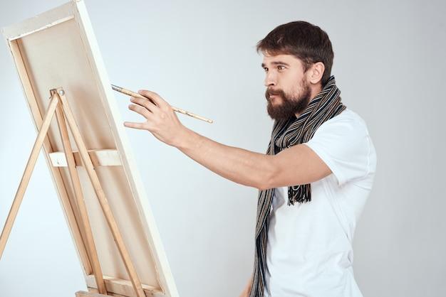 Een man kunstenaar tekent op een ezel een sjaal wit t-shirt kunst hobby creativiteit