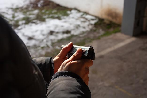 Een man laadt een pistool opnieuw. winter, de deur uit, schietbaan