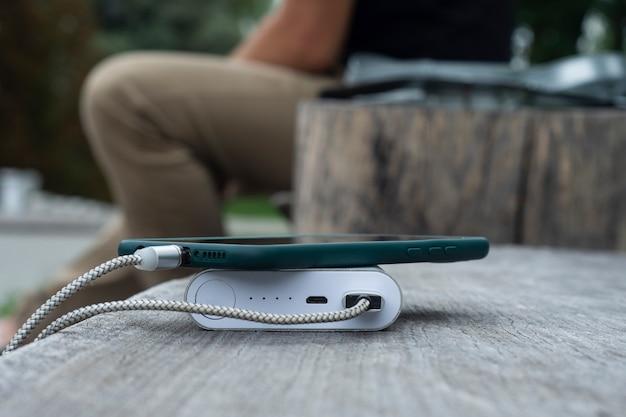 Een man laadt een smartphone op met een powerbank op een houten bankje.