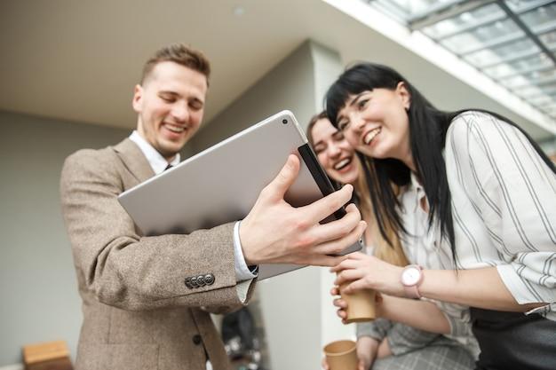 Een man laat iets op zijn grote tablet zien aan twee lachende meisjes