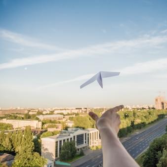 Een man lanceert een papieren vliegtuig in de lucht boven de stad