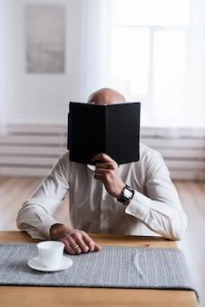 Een man leest iets in een zwart notitieboekje. het concept van freelance, werk op kantoor