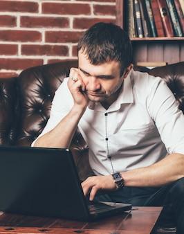 Een man leest informatie van een laptop op de achtergrond van een stijlvolle kamer.