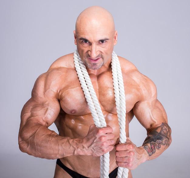 Een man legde een touw om zijn nek en trok zijn spieren aan.