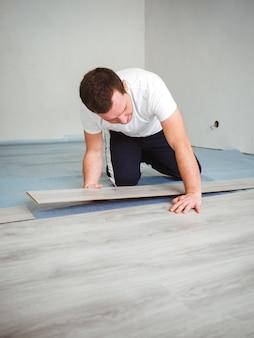 Een man legt een laminaatvloer. het reparatieproces in de kamer