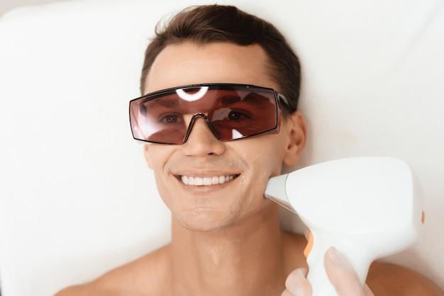 Een man ligt in een bril en lacht in de kliniek.