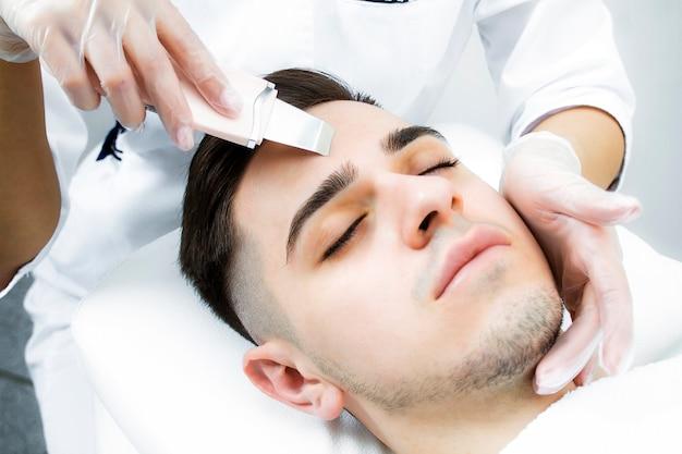 Een man ligt op de procedure voor het reinigen van zijn gezicht met acne met gesloten ogen.