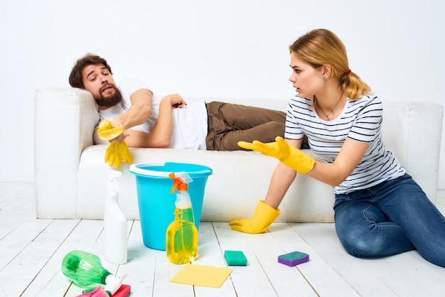 Een man ligt op een bank. een vrouw ruimt huishoudelijke schoonmaakmiddelen op