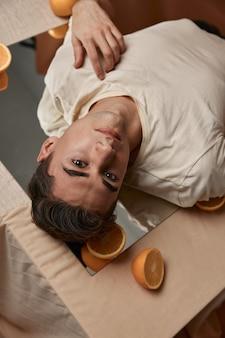 Een man ligt op een tafel op een spiegel sinaasappels aantrekkelijk uiterlijk zelfvertrouwen model. hoge kwaliteit foto