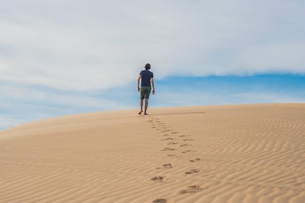Een man loopt in de woestijn van vietnam, mui ne