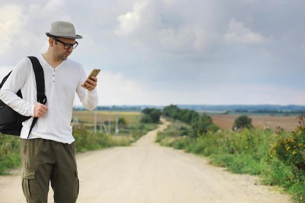 Een man loopt langs een landweg. lifter door het hele land. een man stopt een passerende auto op de weg.