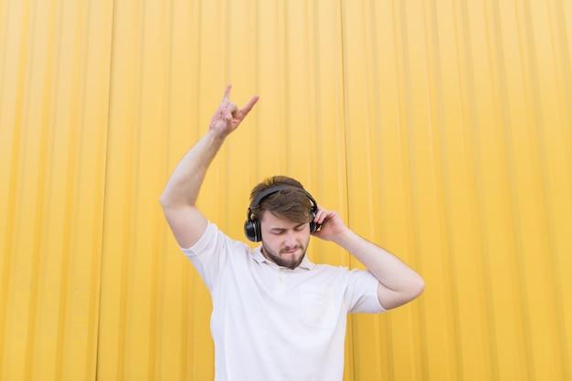 Een man luistert naar rockmuziek in een koptelefoon op een gele muur en toont een bord van heavy metal. zwaar metalen symbool