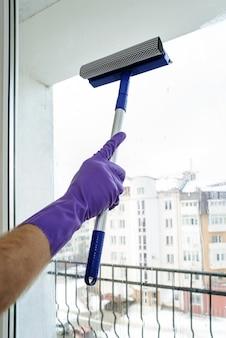 Een man maakt de ramen schoon.