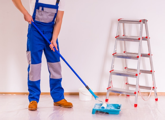 Een man maakt de vloer schoon na reparatie.