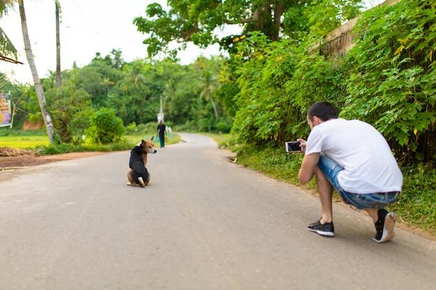 Een man maakt een foto van een hond die midden op de weg zit en naar een halve draai kijkt