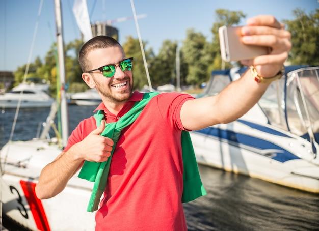 Een man maakt een foto voor het jacht en glimlacht.