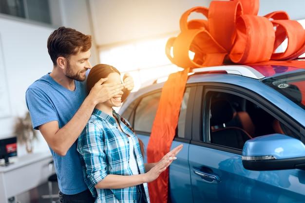 Een man maakt een geschenk - een auto voor zijn vrouw.