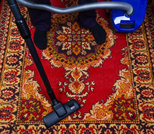 Een man maakt een oud tapijt schoon met een elektrische stofzuiger