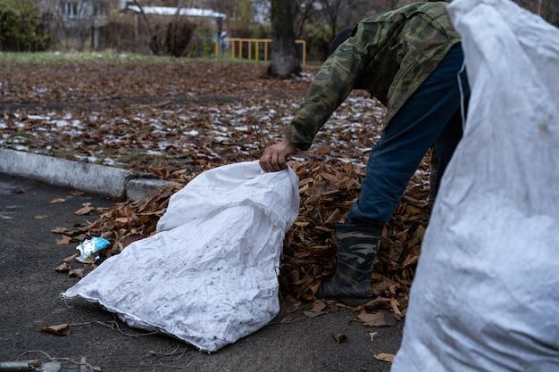 Een man maakt een tuin schoon en veegt