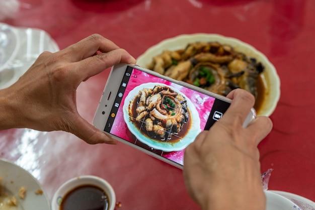 Een man maakt foto's met een mobiele telefoon in zijn hand