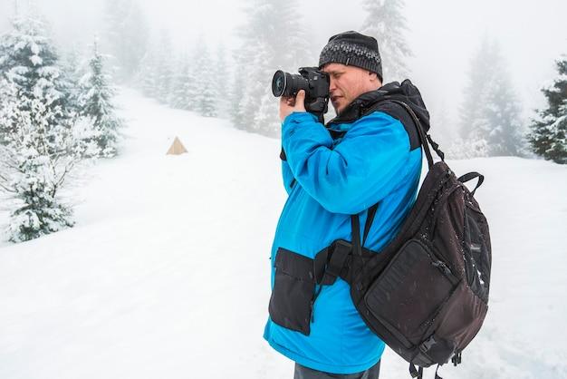 Een man maakt foto's van iets of iemand die in een besneeuwd bos staat. prachtige winterse natuur. fotograaf in het besneeuwde bos