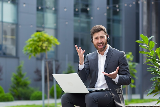 Een man maakt ruzie en gefrustreerd praten op video, met behulp van een laptop en een headset met een microfoon, een boze supporter zittend op een openbare plaats in de buurt van het kantoorcentrum