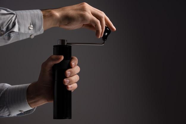 Een man maalt graankoffie met een handmatige koffiemolen. donkere achtergrond. Premium Foto
