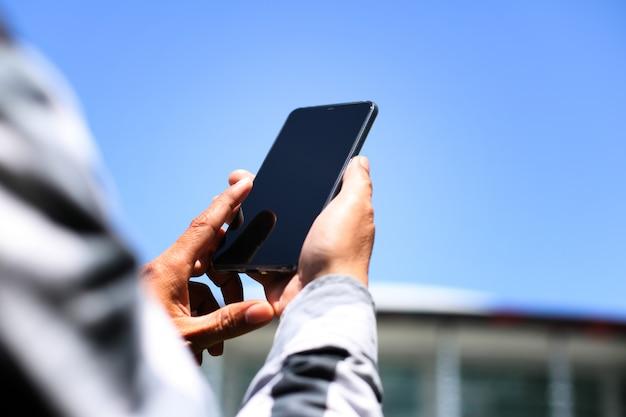 Een man met behulp van smartphone voor het kantoorgebouw.